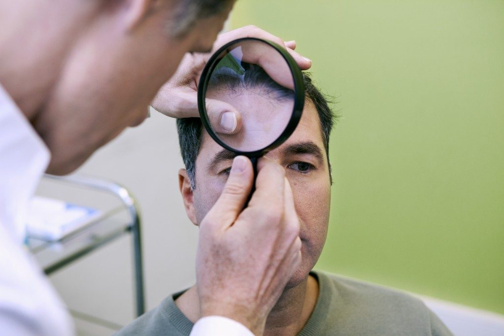 Doctor checking a man's hairline