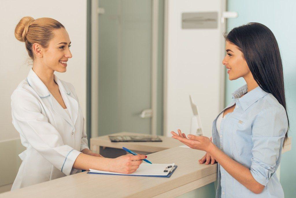 Patient talking to receptionist