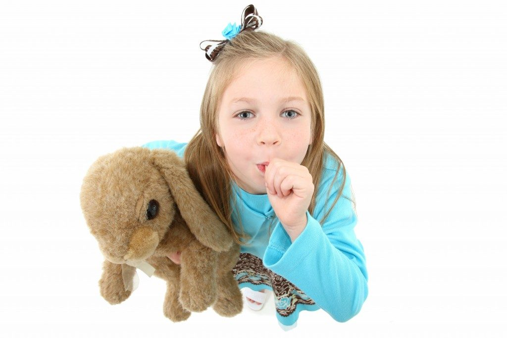Girl holding a stuffed toy while sucking thumb