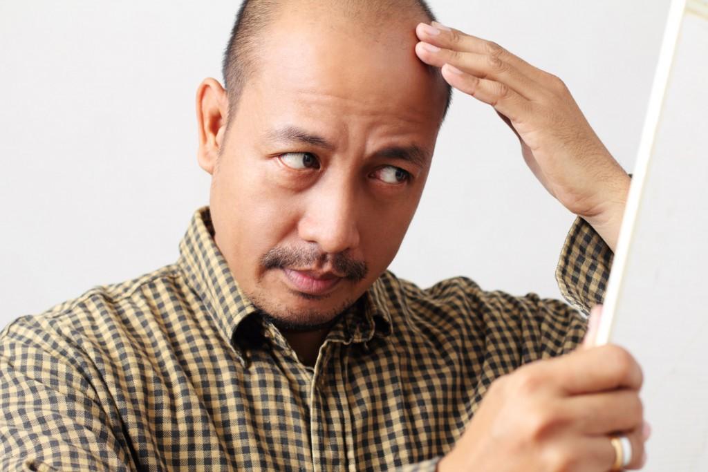 Man checking his thinning hair