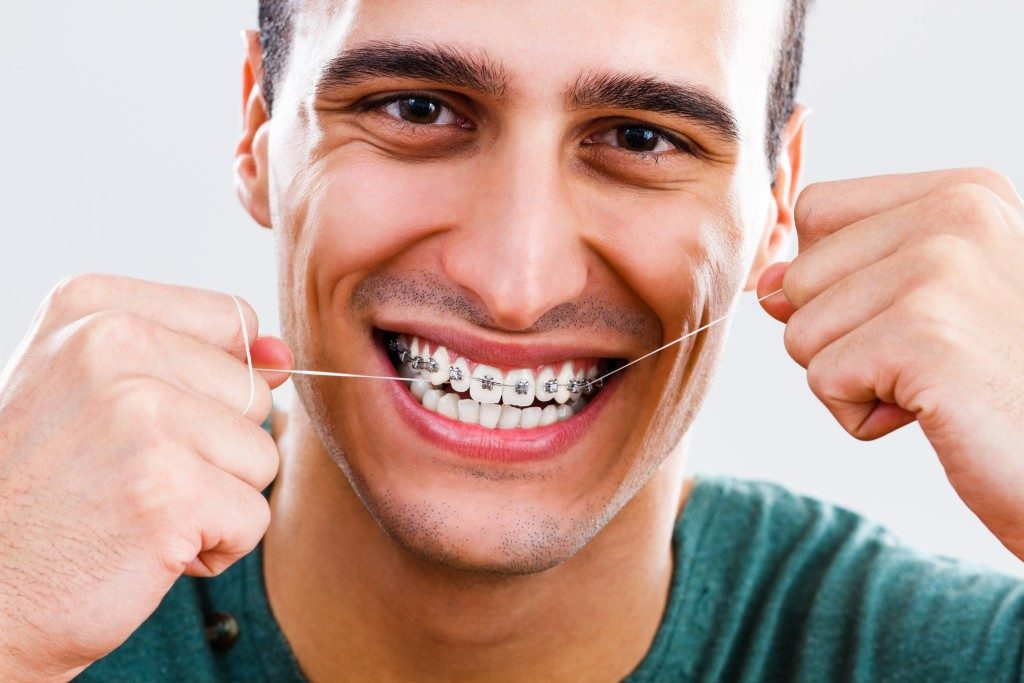 Man with braces flossing