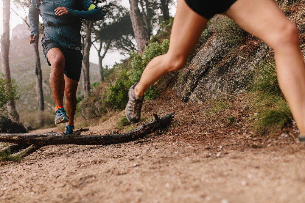 Young man and woman jogging on country path, focus on legs