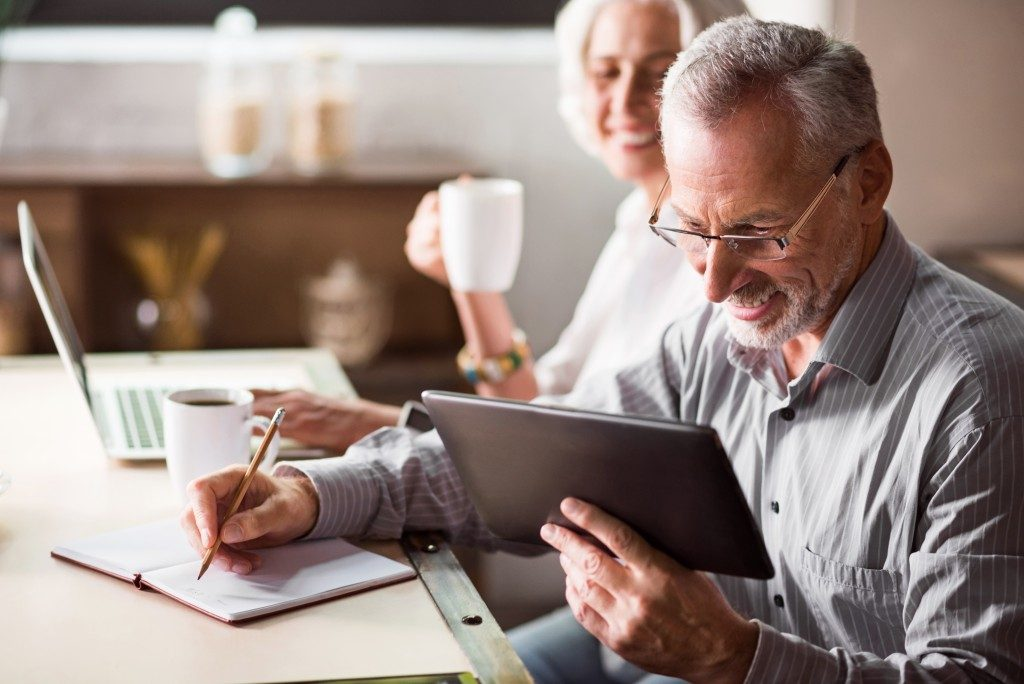 senior couple using a laptop and tablet