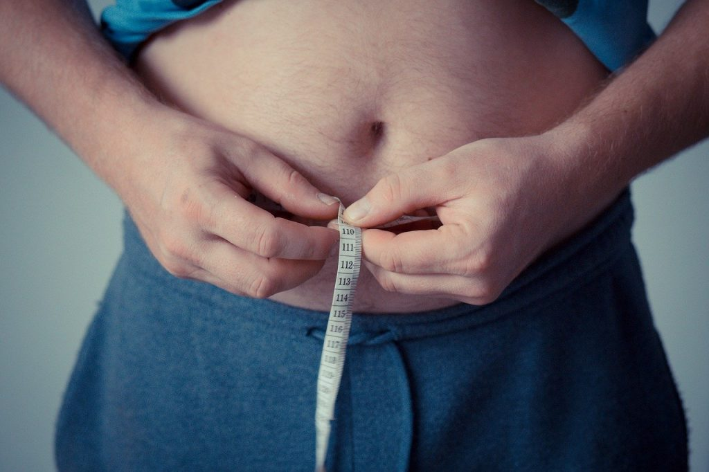 person measuring belly fat