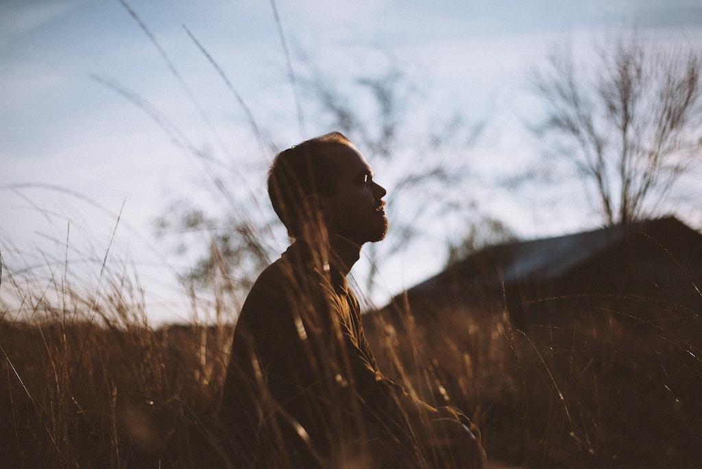 Man meditating in a field