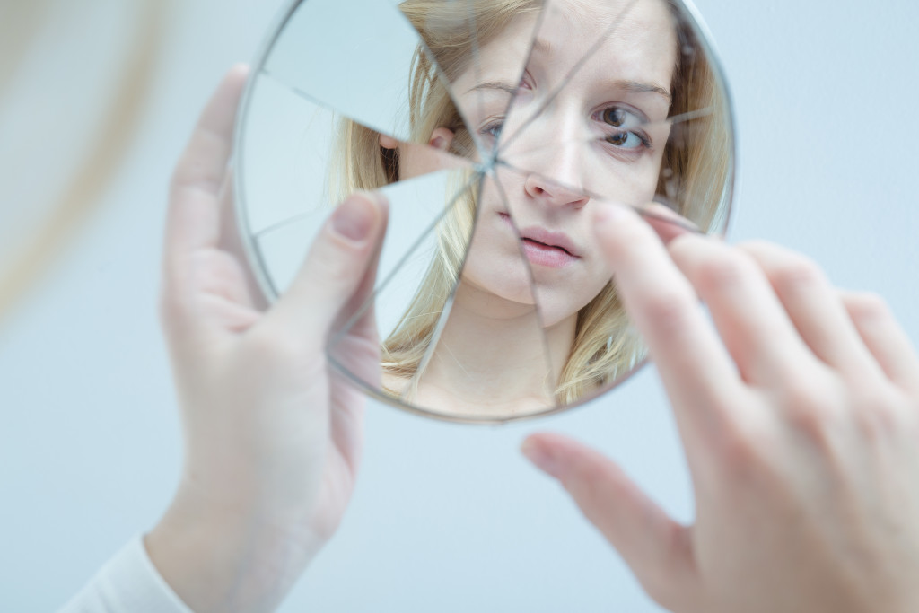 woman looking at a broken mirror